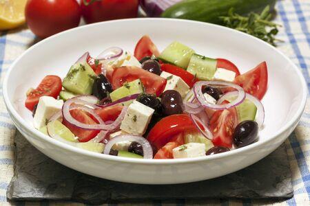 kalamata: Greek salad in white bowl, with ingredients behind.