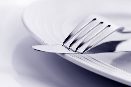 shallow focus: Knife and fork on white plate, in soft focus