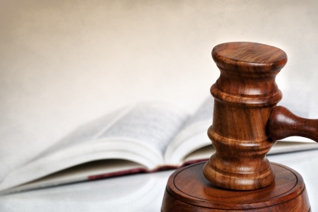 criminal law: Wooden gavel with blurred law book behind   Lots of copy-space  Stock Photo