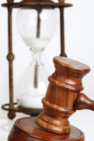 justice hammer: Gavel and block, with antique hourglass behind