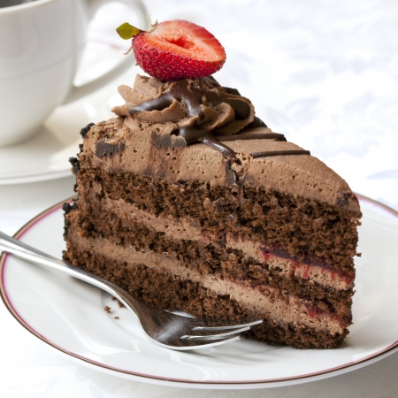 coffee and cake: Chocolate cake topped with a strawberry, served with coffee