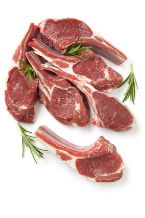 Raw lamb cutlets with rosemary sprigs, isolated on white