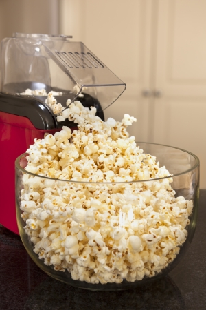 bowls of popcorn: Bowl of popcorn with popcorn machine on a kitchen bench   Healthy home-made snacking  Stock Photo