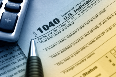 preparations: US tax form 1040 with pen and calculator