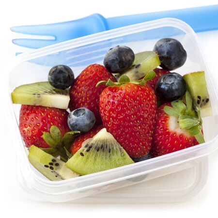 lunch box: Fruit salad in a plastic lunch box, with fork   Strawberries, blueberries and kiwi fruit  Stock Photo