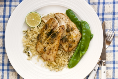cooked fish: Grilled fish fillets with cous cous and snow peas   Garnished with dill, capers and lime