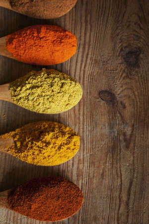 indian spice: Spices on wooden spoons, over old timber  Stock Photo