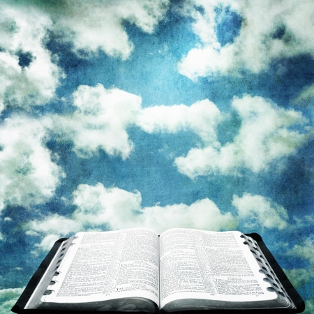 Open Bible over cloudy sky with grunge effects