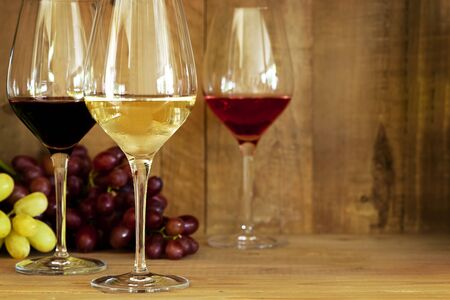 sauvignon blanc: Wine glasses with grapes, against oak background   Includes red, white, and rose