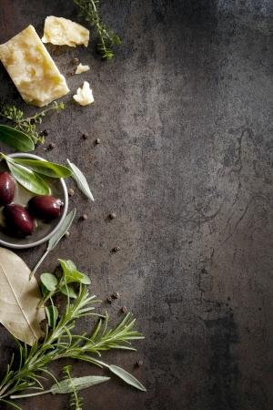 Essen Hintergrund mit Parmesan-Käse, frischen Kräutern und Oliven, über dunklen Schiefer Viel Kopie Platz