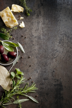 overhead view: Food background with parmesan cheese, fresh herbs and olives, over dark slate   Lots of copy space