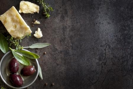 Essen Hintergrund mit Parmesan-Käse, frischen Kräutern und Oliven, über dunklen Schiefer Viel Kopie Platz Standard-Bild