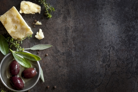 Food background with parmesan cheese, fresh herbs and olives, over dark slate   Lots of copy space