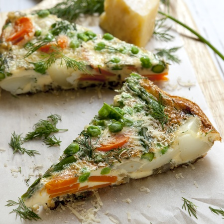 omelet: Wedges of vegetable frittata on a board, with parmesan and dill