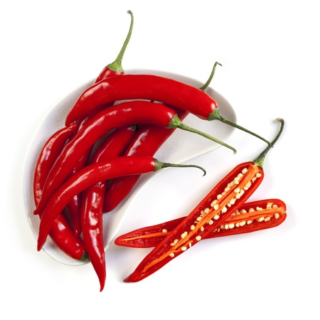 Red hot chili peppers, whole and cut, isolated on white   Overhead view  photo