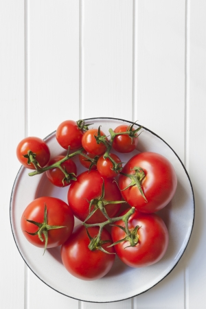 Vine tomatoes in rustic enamel bowl over white timber   Lots of copy space  photo