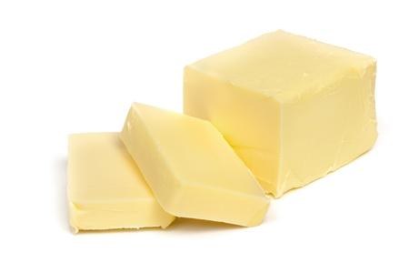 Panetto di burro, tagliato, isolato su bianco.