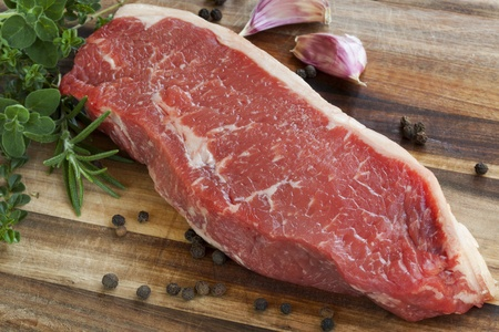 sirloin steak: Raw red sirloin steak with fresh herbs, garlic and peppercorns.