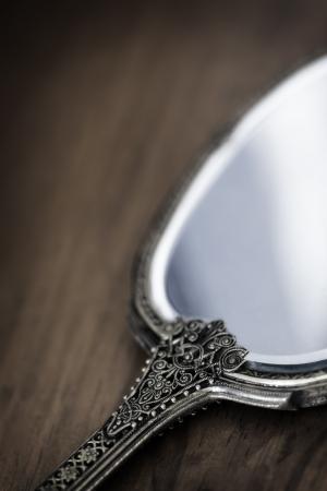 hand mirror: Antique gilded hand mirror, over dark timber.  Soft focus.