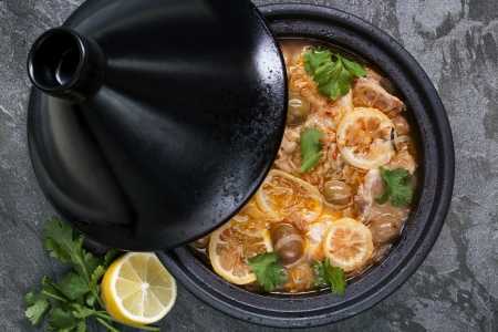 stew pan: Chicken cooking in traditional tagine   With lemons, green olives and cilantro