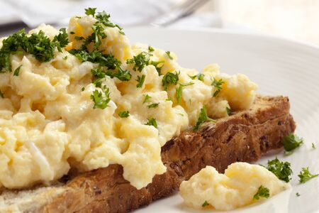Scrambled eggs on toasted wholegrain bread.  Garnished with parsley.