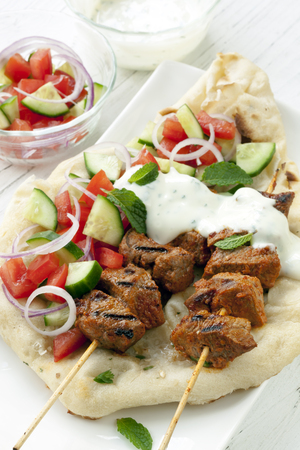minted: Tandoori lamb kebabs with naan bread, salad, and minted yogurt. Stock Photo