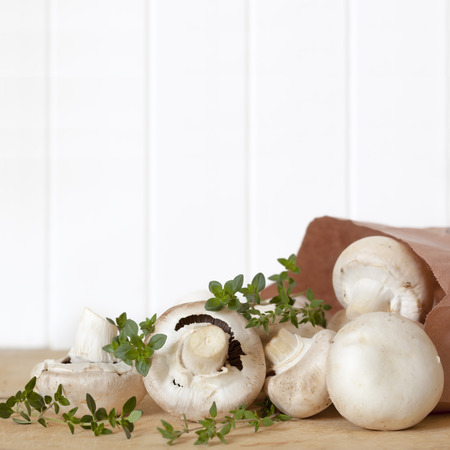 Mushrooms spilling from brown paper bag, with fresh thyme   Room for text  photo