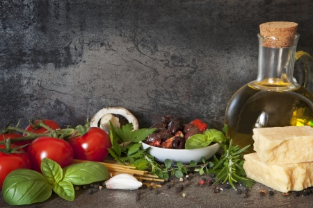 Italian food background, with vine tomatoes, basil, spaghetti, mushrooms, olives, parmesan, olive oil, garlic, peppercorns, rosemary, parsley and thyme    Stock Photo