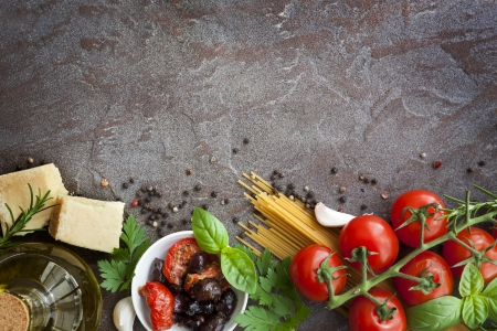 Italian food background, with vine tomatoes, basil, spaghetti, mushrooms, olives, parmesan, olive oil, garlic, peppercorns, rosemary, parsley and thyme   Slate background