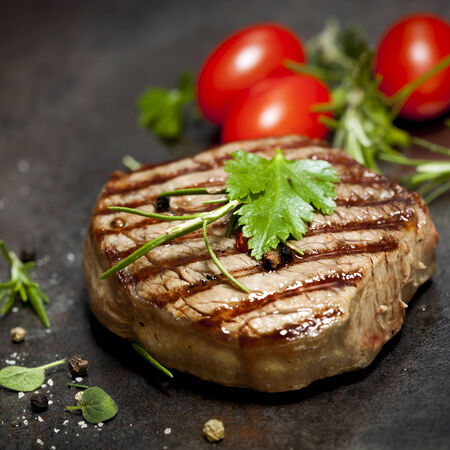 Grilled steak with herbs and tomatoes, on dark slate. photo