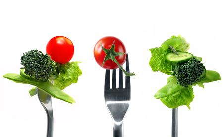 Forkfuls von gesunden Lebensmitteln auf weißem Hintergrund.