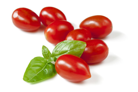 Baby plum tomatoes with basil, isolated on white.
