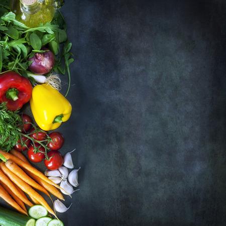 Essen Hintergrund mit Salatzutaten über dunklem Schiefer. Overhead Ansicht.