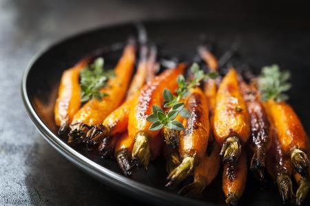 Ofen Baby-Karotten mit Thymian, in schwarze Platte auf Schiefer.