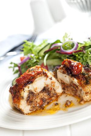 Stuffed chicken breast with salad.  Sundried tomato and mozzarella filling. photo