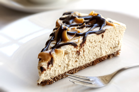 Slice of chocolate caramel cheesecake, in soft focus. Imagens