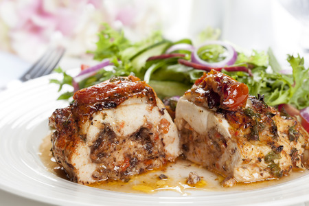 Stuffed chicken breast with salad.  Sundried tomato and mozzarella filling. photo