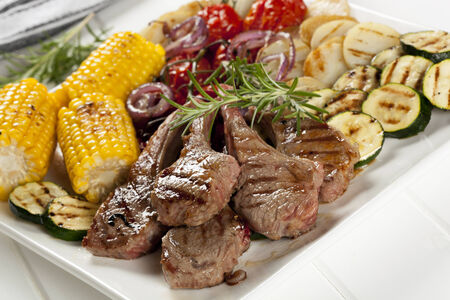 lowfat: Serving platter of barbecued lamb cutlets and grilled vegetables. Stock Photo