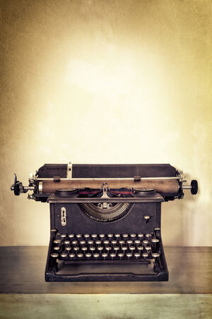Vintage typewriter on old desk with grunge background.  Lots of copy space. photo