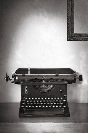 Vintage typewriter on old desk with grunge background.  Lots of copy space. Black and White. photo