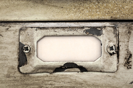 filing cabinet: Close up of blank label in metal holder of vintage filing cabinet.  Great grunge textures. Stock Photo