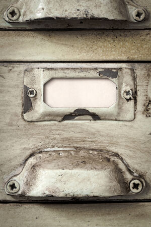 Close up of blank label in metal holder of vintage filing cabinet.  Great grunge textures. photo