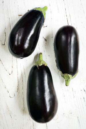 directly above: Three aubergine or eggplants on rustic white timber.  Overhead view.