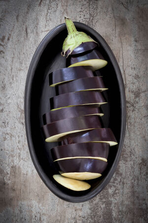 directly above: Sliced eggplant or aubergine in black dish.  Overhead view, over old timber. Stock Photo