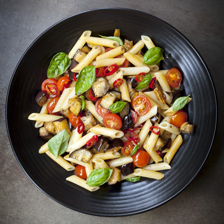 overhead view: Eggplant, chilli and tomato penne pasta, on a black serving platter.  Garnished with basil. Stock Photo