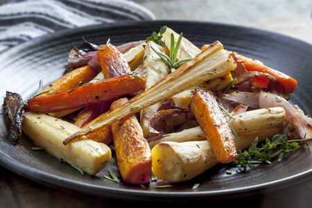 parsnips: Roasted root vegetables on a black serving platter.  Carrots, parsnips, turnips, red onions, and herbs. Stock Photo