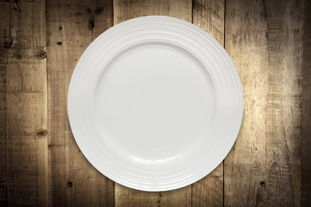 top down: Empty white round plate over rustic grunge wood panels.