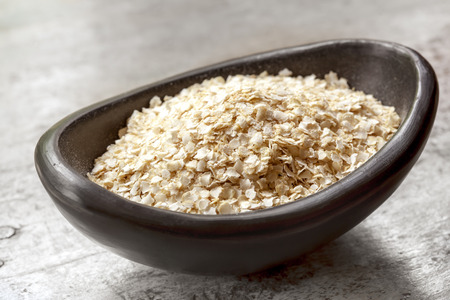flake: Quinoa flakes in small black bowl over rustic wood.