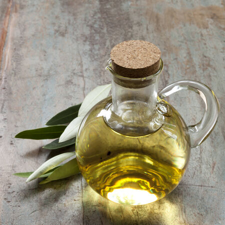foglie ulivo: Bottiglia di olio d'oliva con foglie di ulivo, oltre legno rustico.