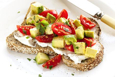 wholegrain: Toast with cream cheese, avocado and cherry tomatoes.